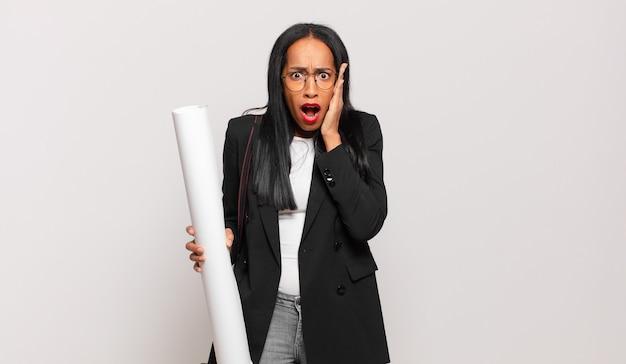 Jonge zwarte vrouw voelt zich geschokt en bang, ziet er doodsbang uit met open mond en handen op de wangen. architect concept