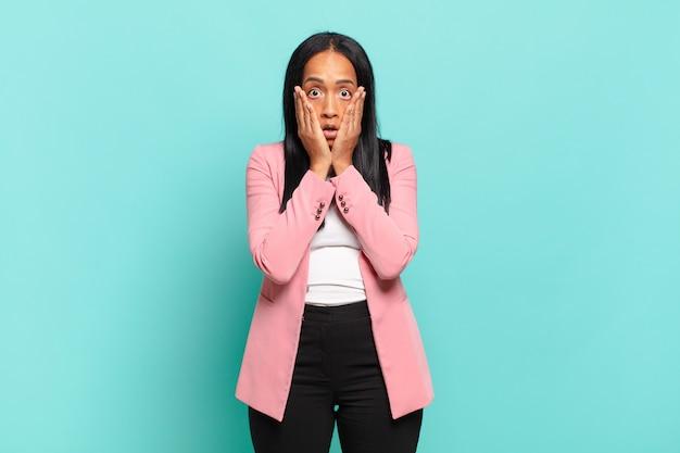 Jonge zwarte vrouw voelt zich geschokt en bang, ziet er doodsbang uit met open mond en handen op de wangen. bedrijfsconcept
