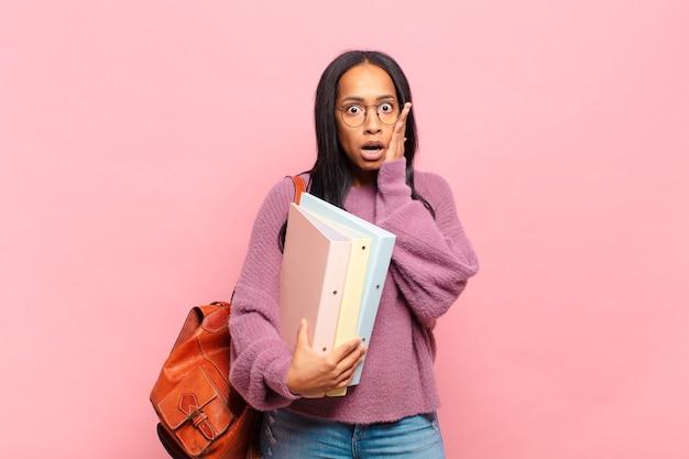 Jonge zwarte vrouw voelt zich geschokt en bang, ziet er doodsbang uit met open mond en handen op de wangen. studentenconcept