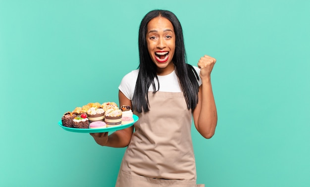 Jonge zwarte vrouw voelt zich geschokt, opgewonden en gelukkig, lacht en viert succes en zegt wow!. bakkerij chef-kok concept