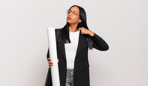 Jonge zwarte vrouw voelt zich gestrest, angstig, moe en gefrustreerd, trekt aan de nek van het shirt, ziet er gefrustreerd uit met een probleem. architect concept