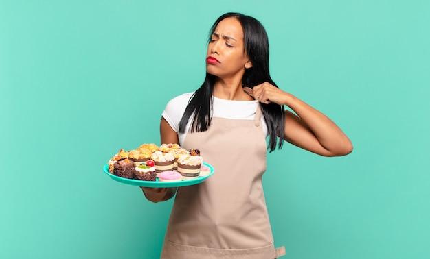 Jonge zwarte vrouw voelt zich gestrest, angstig, moe en gefrustreerd, trekt aan de nek van het shirt, ziet er gefrustreerd uit met een probleem. bakkerij chef-kok concept