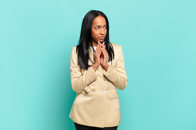 Jonge zwarte vrouw voelt zich trots, ondeugend en arrogant terwijl ze een kwaadaardig plan bedenkt of een truc bedenkt.
