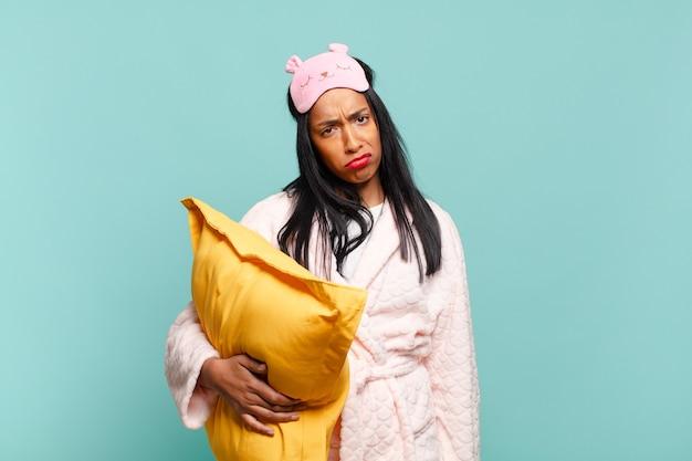 Jonge zwarte vrouw voelt zich verdrietig en zeurt met een ongelukkige blik, huilend met een negatieve en gefrustreerde houding. pyjama concept