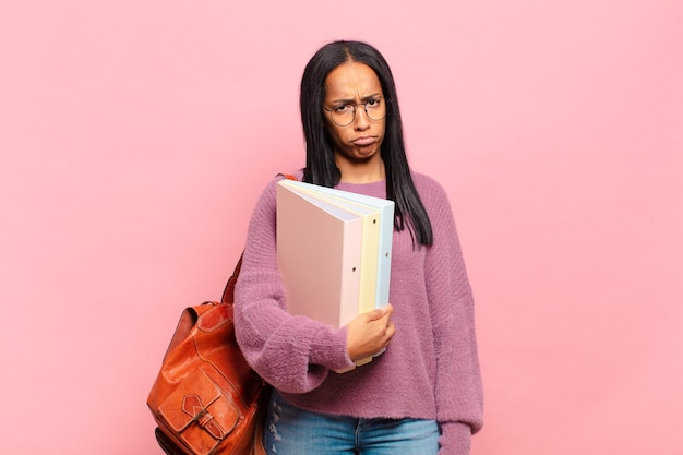 Jonge zwarte vrouw voelt zich verdrietig en zeurt met een ongelukkige blik, huilend met een negatieve en gefrustreerde houding. studentenconcept