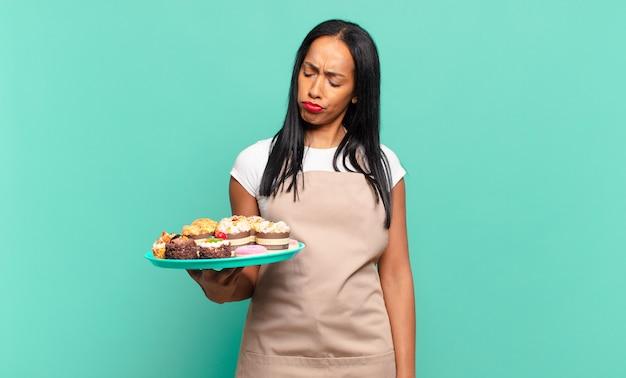 Jonge zwarte vrouw voelt zich verdrietig, overstuur of boos en kijkt opzij met een negatieve houding, fronsend in onenigheid. bakkerij chef-kok concept