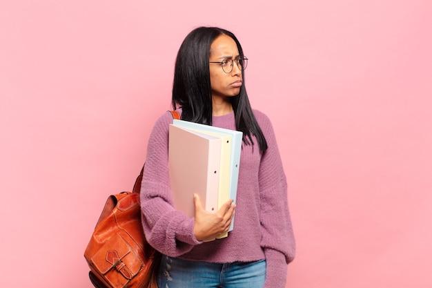 Jonge zwarte vrouw voelt zich verdrietig, overstuur of boos en kijkt opzij met een negatieve houding, fronsend in onenigheid. studentenconcept