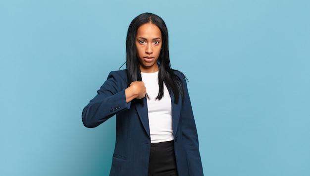 Jonge zwarte vrouw voelt zich verward, verbaasd en onzeker, wijst naar zichzelf en vraagt zich af wie, ik?. bedrijfsconcept
