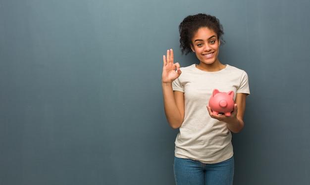 Jonge zwarte vrouw vrolijk en vol vertrouwen doet ok gebaar. ze houdt een spaarvarken vast.