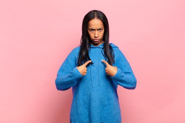Jonge zwarte vrouw wijst naar zichzelf met een verwarde en vragende blik, geschokt en verrast om gekozen te worden
