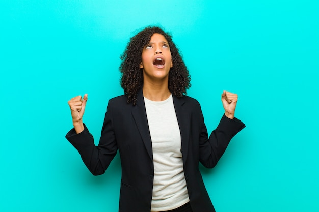Jonge zwarte vrouw woedend schreeuwen, zich gestrest en geïrriteerd voelen met handen omhoog in de lucht en zeggen waarom ik tegen de blauwe muur