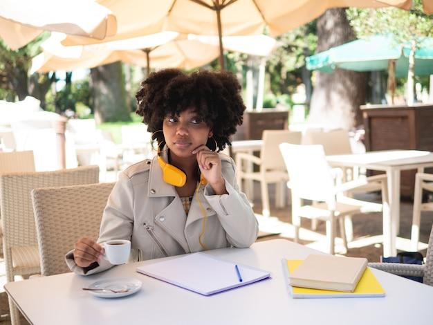 Jonge zwarte vrouw zat aan een tafel in een coffeeshop terwijl ze wat papierwerk deed, buitenshuis