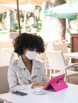Jonge zwarte vrouw zat in een coffeeshop terwijl ze aan het werk was met een roze tablet
