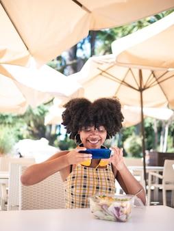 Jonge zwarte vrouw zat op een terras en nam een foto naar een groene salade, gezond voedselconcept