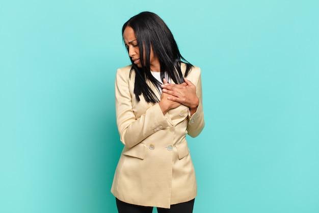 Jonge zwarte vrouw ziet er verdrietig, gekwetst en diepbedroefd uit, houdt beide handen dicht bij het hart, huilt en voelt zich depressief. bedrijfsconcept