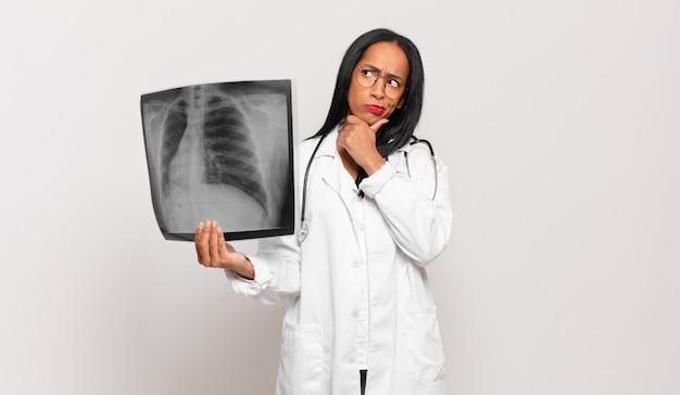 Jonge zwarte vrouwelijke arts denkt, voelt zich twijfelachtig en verward