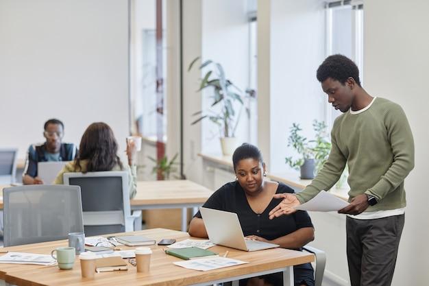 Jonge zwarte zakenman bekritiseert productpresentatie gemaakt door zijn collega