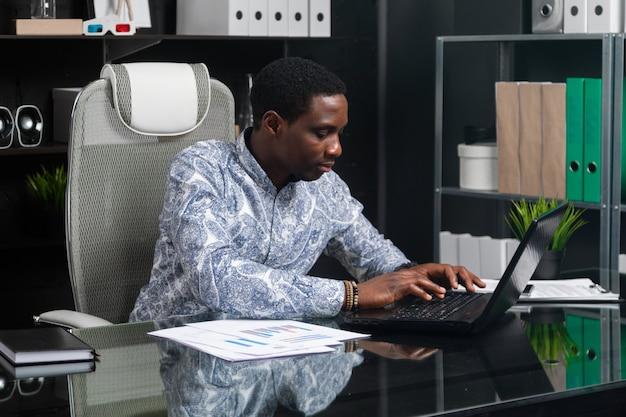 Jonge zwarte zakenman die bij laptop in bureau werkt