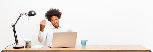 Jonge zwarte zakenman die capice of geldgebaar maken, die u vertellen om uw schulden te betalen