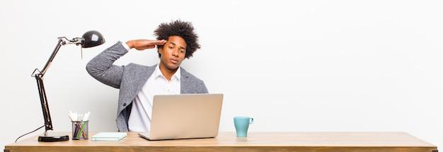 Jonge zwarte zakenman die de camera met een militaire groet in een handeling van eer en patriottisme begroet, die eerbied op een bureau toont