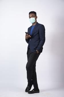 Jonge zwarte zakenman die een pak en gezichtsmasker draagt met zijn telefoon