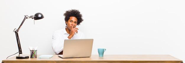 Jonge zwarte zakenman die ernstig en kruis met vinger kijkt die aan lippen wordt gedrukt die stilte eisen of stil, die een geheim op een bureau houden