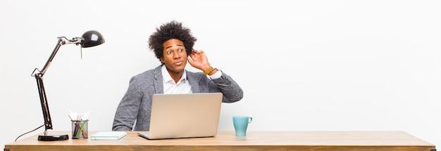 Jonge zwarte zakenman die ernstig en nieuwsgierig kijkt, luistert, probeert een geheim gesprek of roddel te horen, die op een bureau afluistert