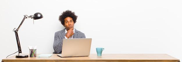 Jonge zwarte zakenman die ernstig, verward, onzeker en nadenkend kijkt, twijfelend onder opties of keuzen op een bureau