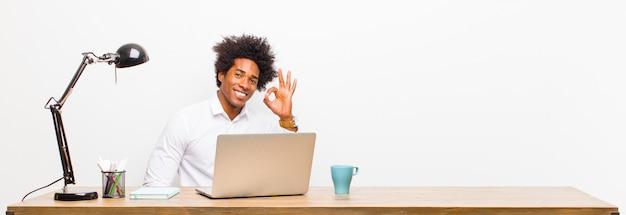 Jonge zwarte zakenman die gelukkig, ontspannen en tevreden voelt, die goedkeuring met ok gebaar toont, dat op een bureau glimlacht