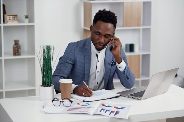 Jonge zwarte zakenman die op mobiele telefoon spreekt en aan laptop in modern wit bureau werkt, exemplaarruimte