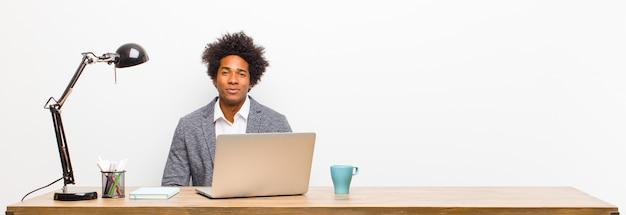 Jonge zwarte zakenman die positief en vol vertrouwen glimlacht, tevreden, vriendelijk en gelukkig op een bureau kijkt