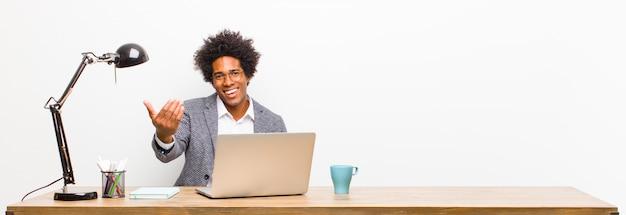 Jonge zwarte zakenman die zich gelukkig, succesvol en zelfverzekerd voelt, voor een uitdaging staat en zegt: kom maar op! of je te verwelkomen op een bureau