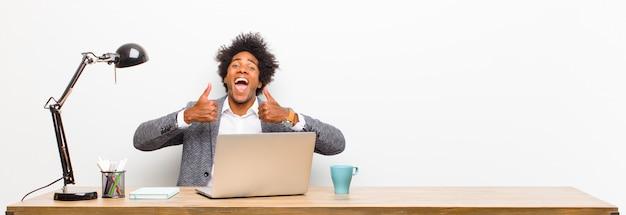 Jonge zwarte zakenman glimlachend breed op zoek gelukkig, positief, zelfverzekerd en succesvol, met beide duimen omhoog op een bureau