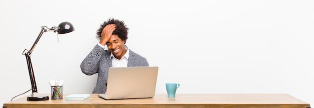 Jonge zwarte zakenman lacht en slaat op het voorhoofd alsof hij zegt dat ik het vergeten ben of dat was een domme fout
