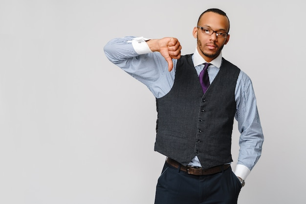 Jonge zwarte zakenman met een afwijkende ernstige afkeer uitdrukking met duimen neer in afkeuring.