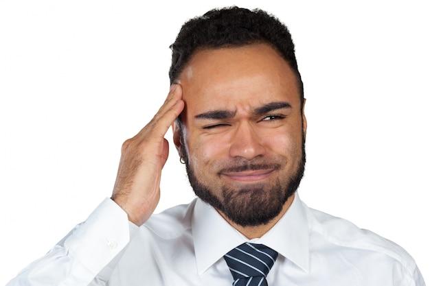 Jonge zwarte zakenman met een hoofdpijn die op witte achtergrond wordt geïsoleerd