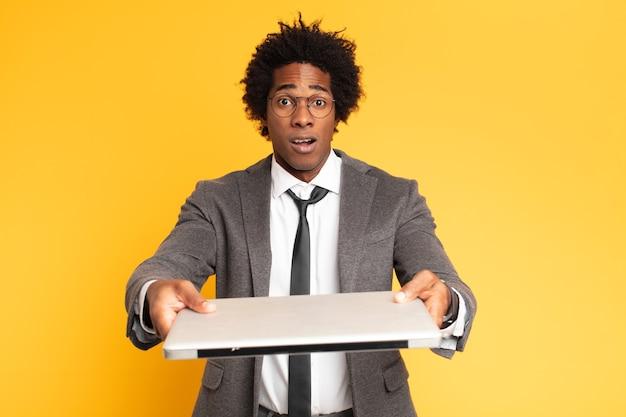 Jonge zwarte zakenman met laptop