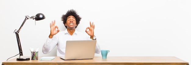 Jonge zwarte zakenman op zoek geconcentreerd en mediteren, tevreden en ontspannen voelen, denken of een keuze maken op een bureau