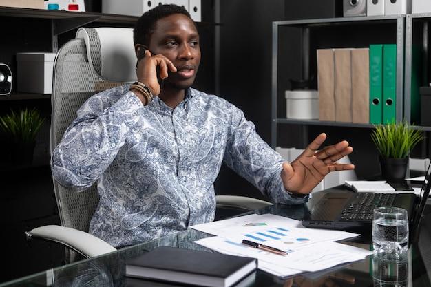 Jonge zwarte zakenman praten op mobiele telefoon zit op computer bureau in kantoor