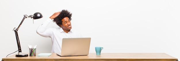 Jonge zwarte zakenman verward en verward gevoel, hoofd krabben en kijken naar de zijkant op een bureau
