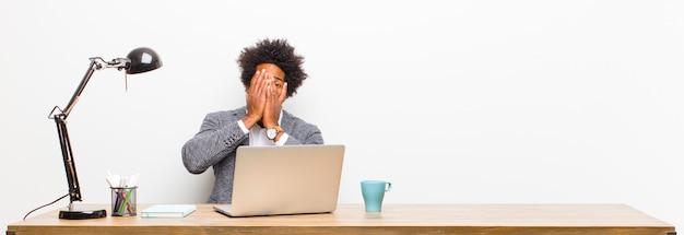 Jonge zwarte zakenman voelt zich bang of beschaamd, gluren of spionage met ogen half bedekt met handen op een bureau