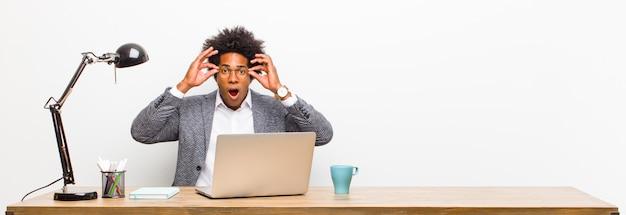 Jonge zwarte zakenman voelt zich geschokt, verbaasd en verrast, met een bril met verbaasde, ongelovige blik op een bureau