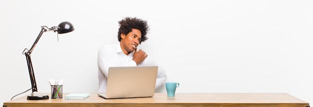 Jonge zwarte zakenman voelt zich moe, gestrest, angstig, gefrustreerd en depressief, lijdend aan rug- of nekpijn op een bureau