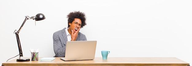 Jonge zwarte zakenman wang houden en lijden aan pijnlijke kiespijn, ziek, ellendig en ongelukkig voelen, op zoek naar een tandarts op een bureau