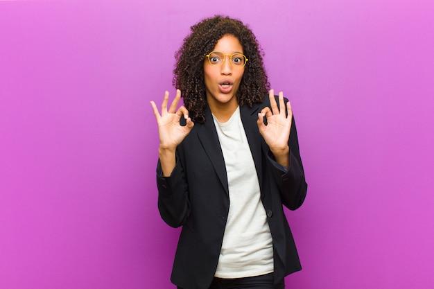 Jonge zwarte zakenvrouw gevoel geschokt, verbaasd en verrast, goedkeuring tonen maken goed teken met beide handen