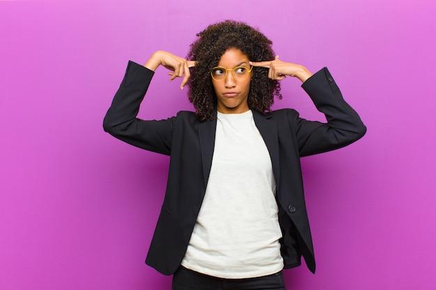 Jonge zwarte zakenvrouw met een serieuze en geconcentreerde blik, brainstormend en denkend aan een uitdagend probleem