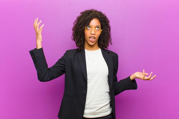 Jonge zwarte zakenvrouw schouderophalend met een domme, gekke, verwarde, verbaasde uitdrukking, geïrriteerd en geen idee