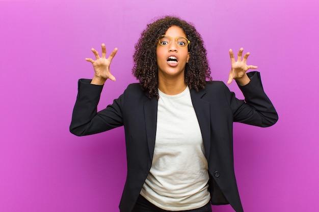 Jonge zwarte zakenvrouw schreeuwen in paniek of woede, geschokt, doodsbang of woedend, met handen naast het hoofd