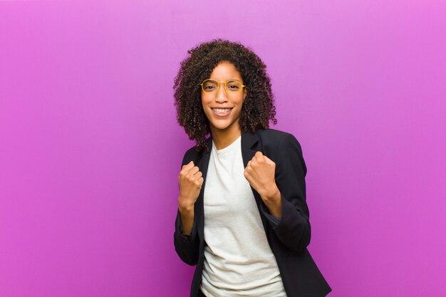 Jonge zwarte zakenvrouw triomfantelijk schreeuwen, lachen en zich gelukkig en opgewonden voelen tijdens het vieren van succes