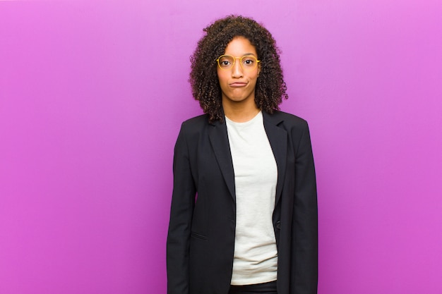 Jonge zwarte zakenvrouw voelt verward en twijfelachtig, vraagt zich af of probeert te kiezen of een beslissing te nemen